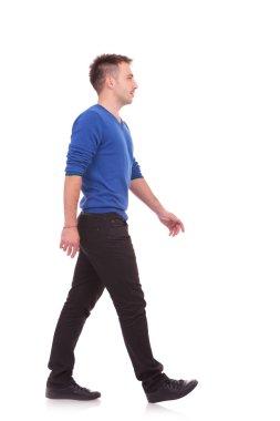 young casual man walking forward