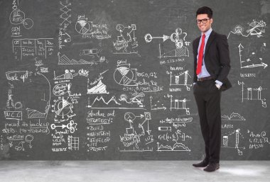 business man stands in front of blackboard