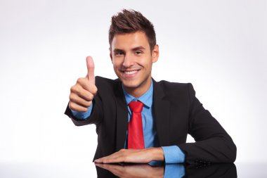 business man at desk showing thumb up