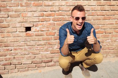Casual man thumbs up by wall