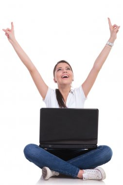 casual woman sits & cheers with laptop