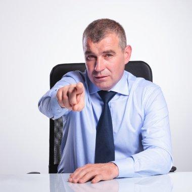 senior business man at desk points at you