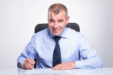 Old business man signs contracts at desk