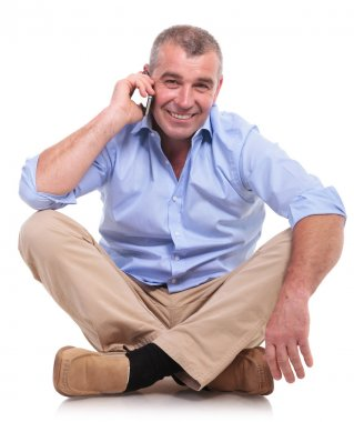casual middle aged man sits and chats on phone