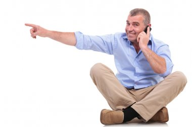 casual old man sits and points while on phone