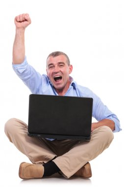 casual old man sits and cheers with laptop