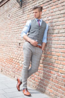 casual man stands next to brick wall