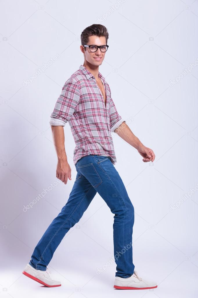 casual man walks to side and looks at you