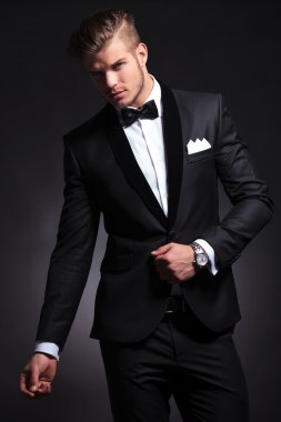 business man posing with hand on tuxedo jacket