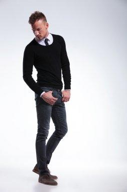 casual man looks down with thumbs in pockets