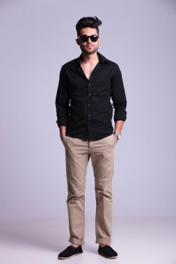 young fashion man stands with hands in pockets