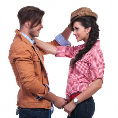casual couple with man taking woman's hat off