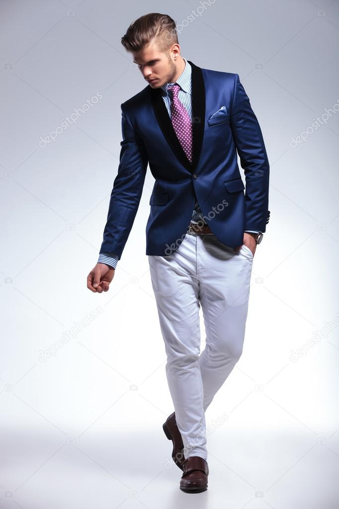young business man walks with hand in pocket