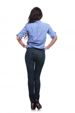 back of a casual woman with hands on hips