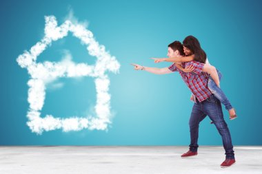 couple pointing to thier dream house made of clouds