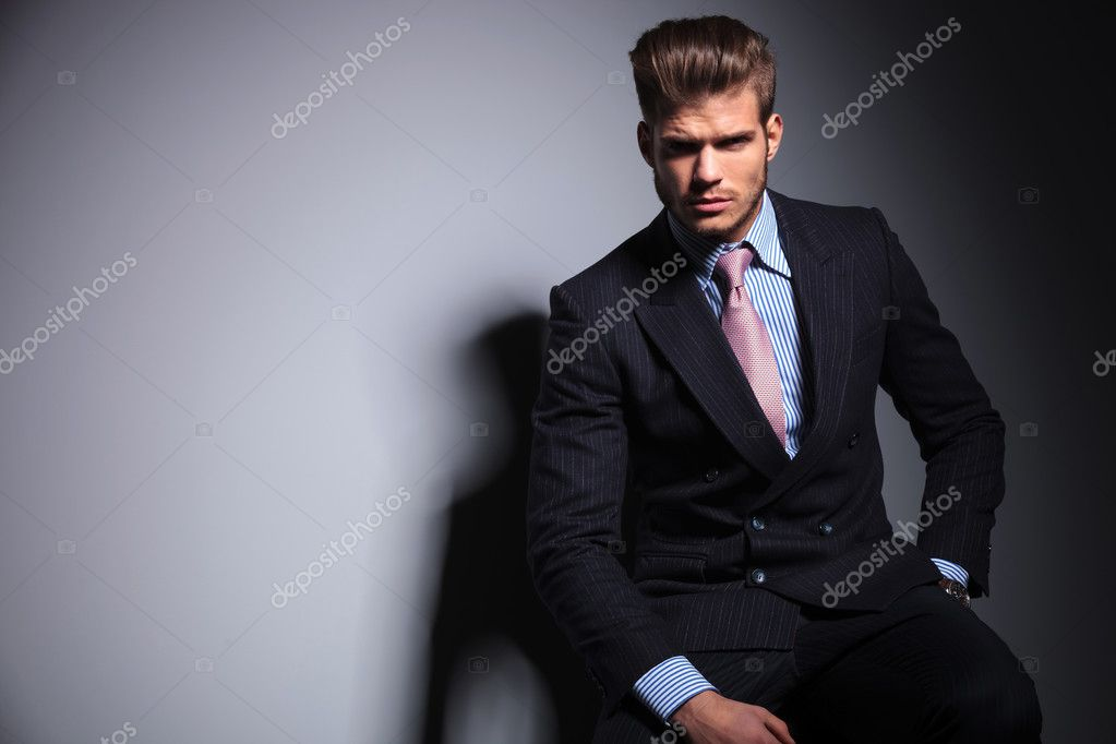 fashion business man in suit and tie is sitting