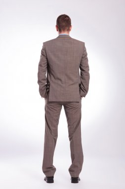 back of a young business man with both hands in pockets