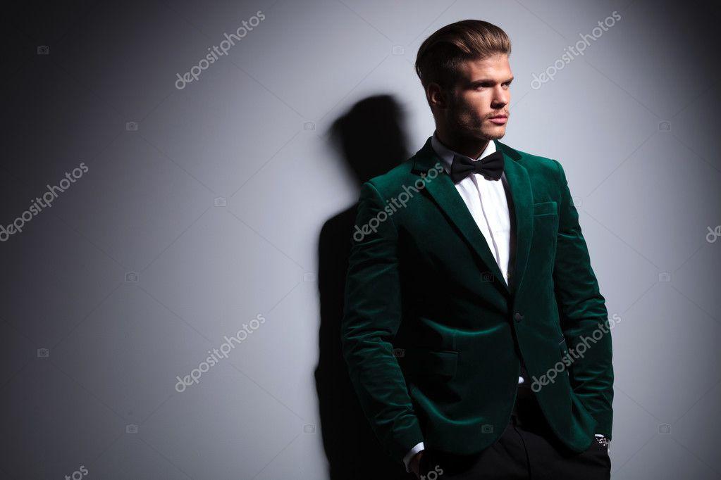 d4a1bc719 Modelo de moda joven relajado en elegante traje de terciopelo verde con  cuello pajarita mirando más allá de la situación de cámara blanco con las  manos en ...