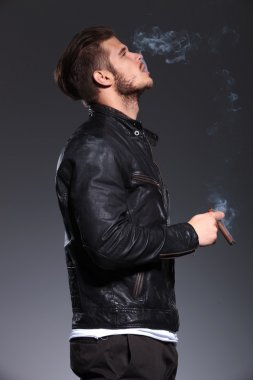 man in leather jacket smoking and blowing the smoke