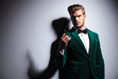 Man in elegant green velvet suit holding a big gun