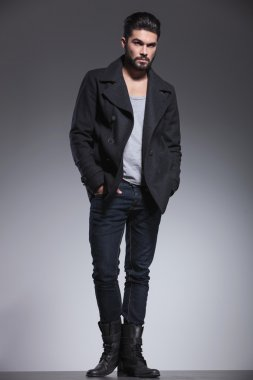 full body picture of a fashion man with beard looking away