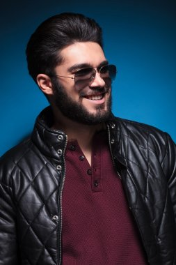 side of a young man with nice hairstyle and beard smiling