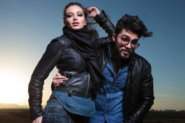 Fashion couple in leather clothes posing outdoor
