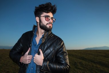 side view of a fashion man holding his leather jacket
