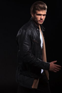 side view of a young man in leather jacket is walking