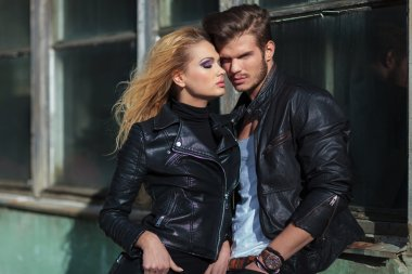 Fashion couple in leather jackets posing against an old building outdoor stock vector