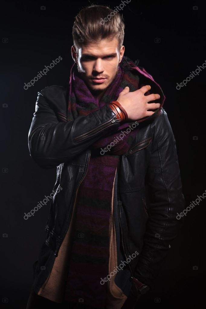 Young Man In Leather Jacket Adjusting His Scarf Stock Photo