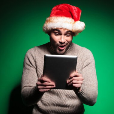 santa man being amazed about what he reads on tablet