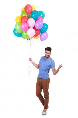 man holding a bunch of baloons is inviting to party