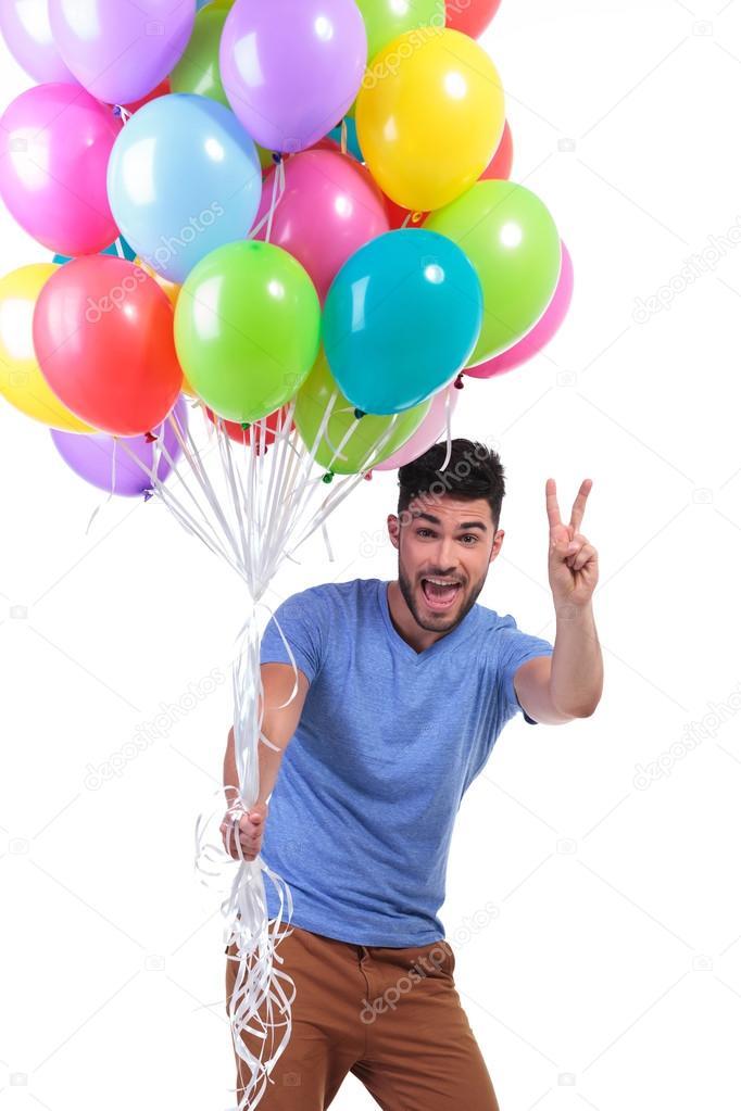 Hombre sosteniendo un manojo de globos y haciendo el signo de la victoria —  Foto de bd1e699e801
