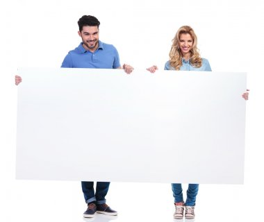 Couple of casual people presenting a big blank billboard