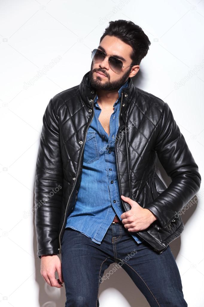 Homme en veste de cuir et lunettes de soleil à la recherche de son côté et  en tirant en veste Fashion — Image de feedough a63c3042f9d