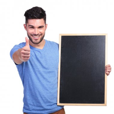 student presenting a blackboard frame and making ok