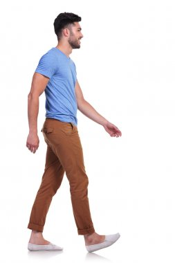 side view of a casual man walking forward and smiling
