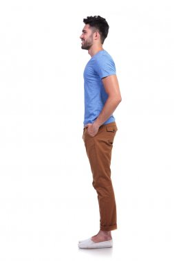 side view of a young casual man standing in line
