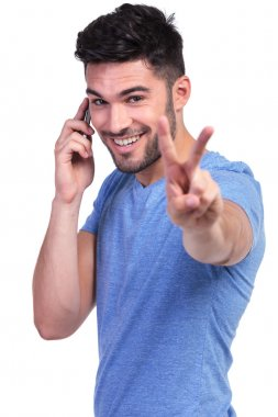 happy casual man making the victory sign on the phone
