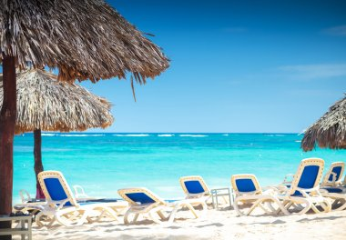 Tropical view of a beach with umbrellas and  beach chairs