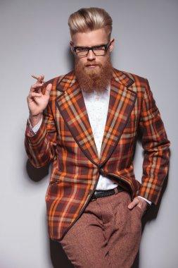 serious fashion man with beard and nice hairstyle smoking