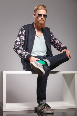 bearded young man sits on small table