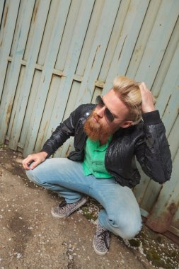 crouched bearded man with hand in hair