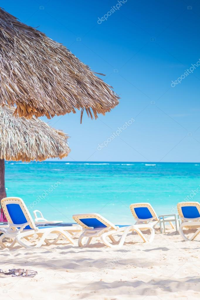 chairs and straw umbrellas on stunning tropical beach