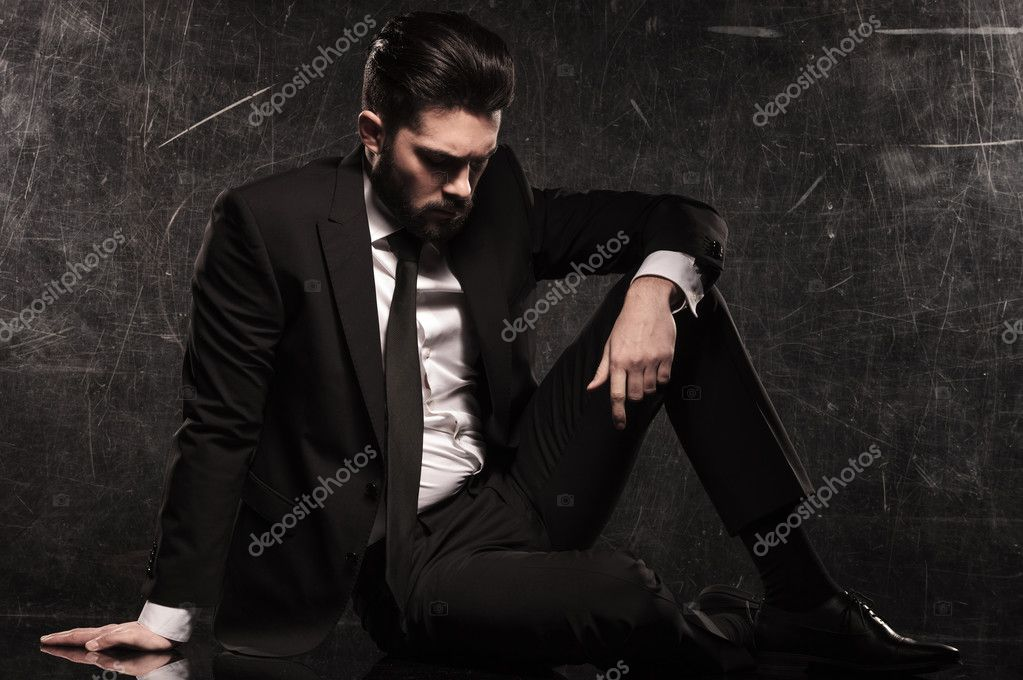 Sad young bearded business man looking down