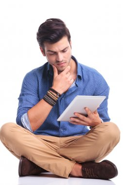 worried young casual man reading on a tablet