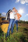 ein junges Paar auf ein altes Auto in einem Feld