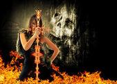 Fotografia donna guerriero con una spada di fuoco con teschio