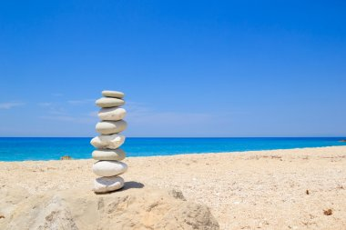Pebbles stack balance over blue sea